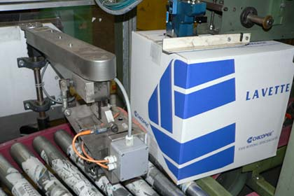 The Padlocker auto case sealer closes the product boxes with tape. Immediately after this, a robotic arm comes into action to glue a barcode label on the box